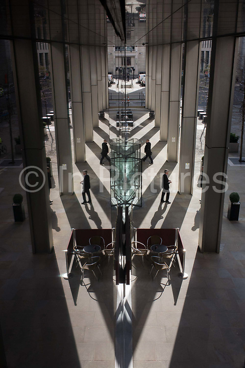 Seen from an aerial viewpoint, office workers come and go from a generic banking company. The symmetrical reflections are reproduced from a dividing line of plate glass in the capital's financial district, known as the City of London - or Square Mile. People come and go from this unidentified building entrance and exit to smoke cigarettes under the shelter of the reflective ceiling. Shadows and light diverge towards the bottom. The City of London is the capital's historic centre first occupied by the Romans then expanded during following centuries until today, it has a resident population of under 10,000 but a daily working population of 311,000.
