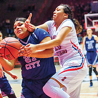 Silver City Fighting Colt Aysia Salas (21), left, and Shiprock Chieftain Aiona Johnson (20) tie up for possession in a District 4A quarterfinal at The Pit in Albuquerque Tuesday.