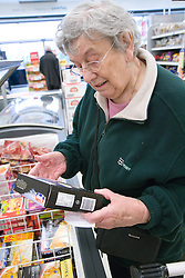 Older woman examining packet food ingredients whilst shopping for groceries in a supermarket,
