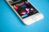 Gold and white Apple iPhone 6 with Twitter log in screen against a blue background