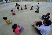 QIANNAN, CHINA - MAY 31: (CHINA OUT) <br /> <br /> Six-pupil School In Mountain Of Qiannan<br /> <br /> The only teacher Wu Guoxian play game with pupils at Gugang primary school in a mountain in Longli County on May 31, 2016 in Qiannan Buyei and Miao Autonomous Prefecture, Guizhou Province of China. Gugang primary school with only one teacher and six students was located in the mountain where the traffic was blocked in Qiannan. 50-year-old Wu Guoxian had been teaching in this school for 33 years and taught over 1,000 students. More and more people went out of the village to work in the cities leaving their children and the old in the mountain. Five under-school-age kids whose parents left for work also stayed at the school. <br /> ©Exclusivepix Media