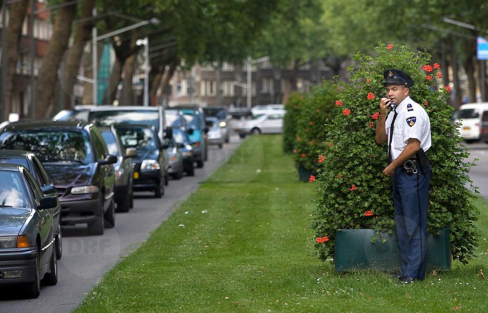 Nederland Rotterdam 29 augustus 2007.Verkeerscontrole op de Dordtse laan. Politie agent heeft zich verdekt opgesteld achter bloempot om automobilisten te betrappen op verkeersovertredingen..Foto David Rozing/