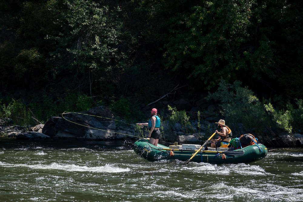 Woman fly fishing from a raft on Oregon's Grande Ronde River.