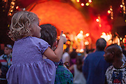 A young girl sits on her father's shoulders to watch Banda Magda, and gives the band a thumbs up.