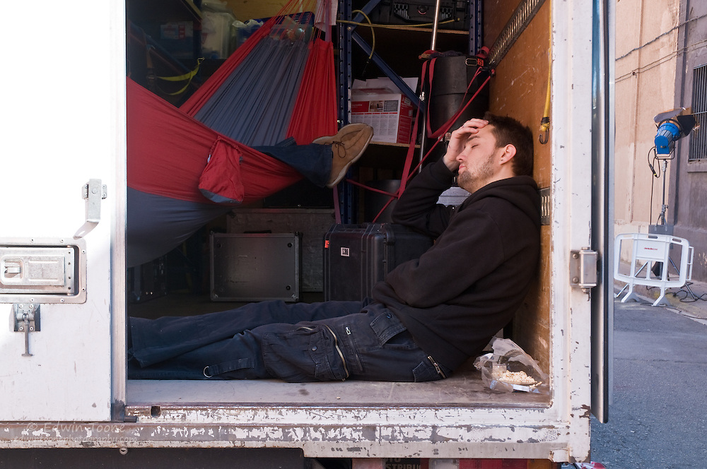 During lunch two crew members take a siesta in the back of an equipment truck.