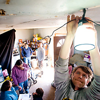 032713     Brian Leddy<br /> Doug Vilsack hangs solar lights in the home of Pauline Wilson near Bodaway Gap Wednesday, March 27. Vilsack runs Eagle Energy, a non-profit that helps install low cost solar installations.