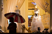 01 JULY 2011 - BANGKOK, THAILAND:  A man stands under an umbrella in front of an upscale wedding shop during a monsoon downpour in Bangkok, Thailand.  PHOTO BY JACK KURTZ