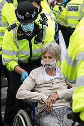 Metropolitan Police officers move a disabled climate activist from Extinction Rebellion who had occupied a road around Parliament Square during a Back The Bill rally on 1st September 2020 in London, United Kingdom. Extinction Rebellion activists are attending a series of September Rebellion protests around the UK to call on politicians to back the Climate and Ecological Emergency Bill (CEE Bill) which requires, among other measures, a serious plan to deal with the UK's share of emissions and to halt critical rises in global temperatures and for ordinary people to be involved in future environmental planning by means of a Citizens' Assembly.