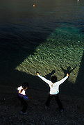 Two children (5 years old, 9 years old) throwing shadows into shallow water. Island of Korcula, Croatia