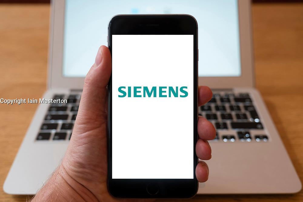Using iPhone smartphone to display logo of Siemens German Multinational conglomerate.