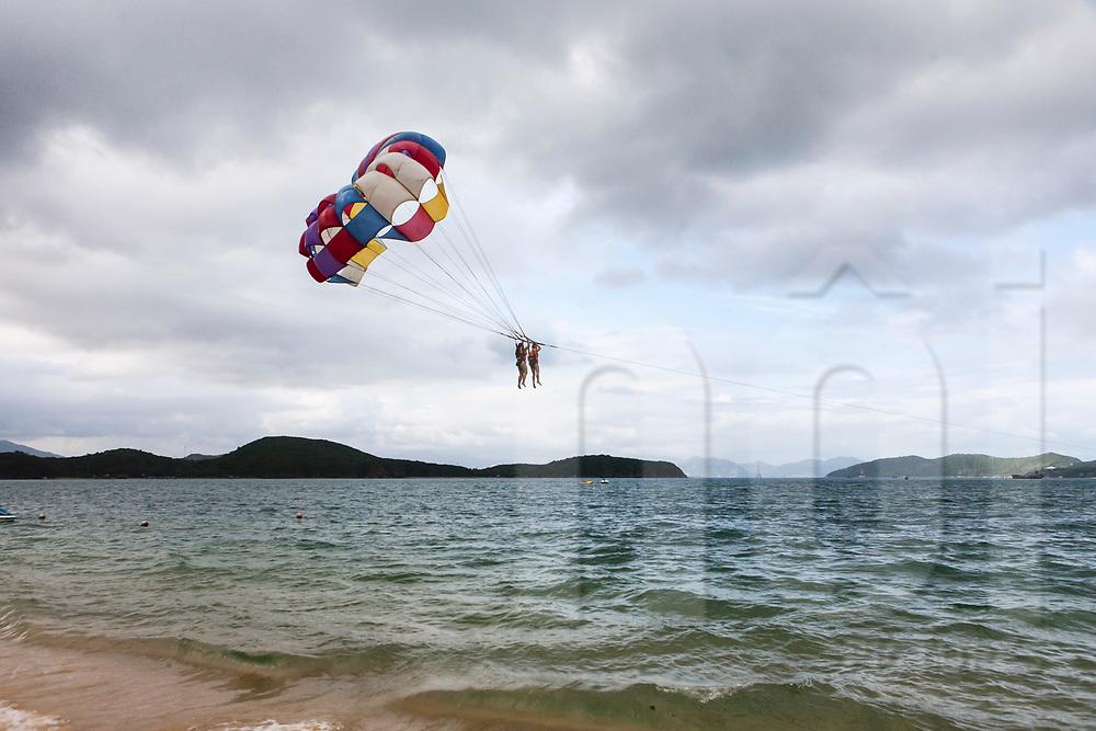 Tourist enjoying parasailing in Nha Trang, Vietnam, Southeast Asia
