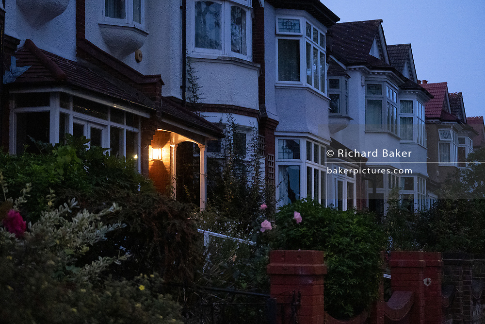 At dawn, a porch light shines in the doorway of a house in a surburban south London home, on 17th September 2020, in London, England.
