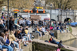 Licensed to London News Pictures. 18/04/2021. London, UK. Pub goers and members of the public soak up the sunshine along the Thames at Richmond, South West London on the first weekend of the easing of Covid-19 restrictions. Shops, pubs, bars and restaurants are now serving customers for the first time in over 4 months as a mini heatwave is set to hit the UK this week with temperatures predicted to reach up to 18c in London and the South East. Photo credit: Alex Lentati/LNP