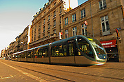 The new modern tram on the posh shopping street Cours de l'Intendence in Bordeaux in evening sun, movement and blurry