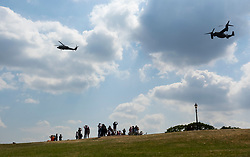 © Licensed to London News Pictures. 12/07/2018. London, UK. People watch from the top of Primrose Hill as President Trump comes into land on Marine One (L) at the Regent's Park home of the US Ambassador at the start of his visit to the UK.  Photo credit: Peter Macdiarmid/LNP