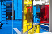 Framed by multicolored glass panels, City workers walk along Lime Street during the lunchtime break in the City of London  the capitals financial district, on 17th June 2019, in London, England. The artwork is entitled Series Industrial Windows I by<br /> Marisa Ferreira and is part of Sculpture in the City 2019.