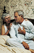 Senior man holds his chest in pain as his concerned wife looks on.