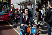 Woman cycling along on a Barclays Cycle Hire Scheme bicycle in central London, UK.