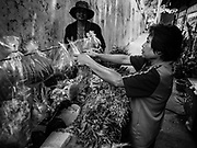 04 JULY 2017 - BANGKOK, THAILAND:  A produce vendor sells fresh vegetable to residents of Pom Mahakan. The final evictions of the remaining families in Pom Mahakan, a slum community in a 19th century fort in Bangkok, have started. An ad hoc group of housing advocates, historic preservationists and academics have asked the city to allow the remaining residents to stay and city officials have said they might allow people who can prove that their families have lived in the fort since before the 1950s, when the city got title to the land from the Thai military, will be able to stay.   PHOTO BY JACK KURTZ