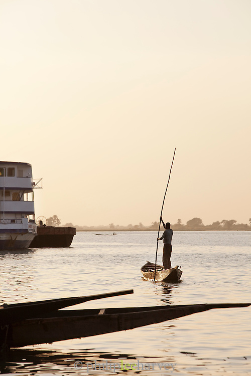 A small fishing boat moves up the Niger River towards a large passenger ferry moored at Segou, Mali