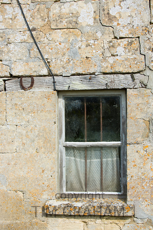 Traditional cottage timber frame window and crumbling old Cotswold stone at Sherborne, The Cotswolds, UK