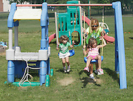 Middletown, New York - A female counselor pushes a girl on a swing in the playground at the Middletown YMCA summer camp on August 20, 2010.