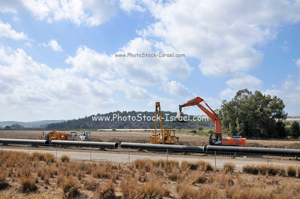 Laying of water pipes. Engineers are placing new water pipes in the ground. Photographed in Israel