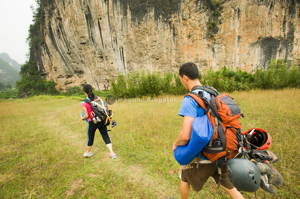 Two rock climbers walk on a grass path to a cliff in China (Model Released, Sean and Rachel Ouyang).