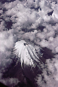 Aerial of Mount Orizaba, a snowcapped volcano in Mexico, from above surrounded by clouds. Shot from a jet.