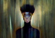 """Black Woman appearing to be emulating from the """"Bush"""".  Green and Yellow, tones with subtle hints of blue."""