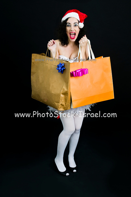 excited Young sexy woman wearing Santa hat does her Christmas shopping