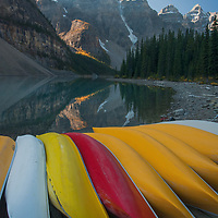 Mounts Babel, Bowlen, Tonsa, Perren & Allen (LtoR) tower above canoes stacked on a dock by Moraine Lake in Banff National Park, Alberta, Canada.