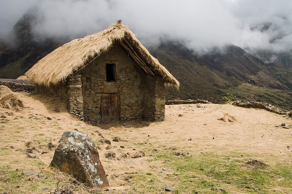 A larger thatch roof stone structure in the traditional village of the Q'eros, high in the Cordillera de Paucartambo, Andes Mountains, Peru. The Q'eros, a Quecha people living in the Peruvian Andes, are considered the last direct descendants of the Incas and proudly maintain many of their ancient traditions.