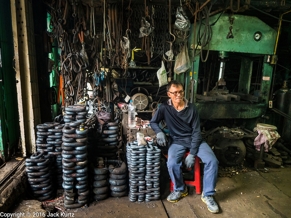25 JANUARY 2016 - BANGKOK, THAILAND:        The worker relaxes in a small one person workshop that makes heavy chains for boat anchors. The metal for the chains is heated until it glows red and then it's pounded into shape. The Talat Noi neighborhood in Bangkok started as a blacksmith's quarter. As cars and buses replaced horse and buggy, the blacksmiths became mechanics and now the area is lined with car mechanics' and blacksmiths' shops.        PHOTO BY JACK KURTZ