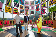 Creative Folkestone director Alastair Upton, Council Leader Cllr David Monk, artist Morag Myerscough, Cabinet Member for the District Economy Cllr David Wimble, and Operations Manager Alastair Clifford at the site of Morag's Flock of Seagulls Bag of Stolen Chips for the Triennial Launch on 20th of July 2021, in Folkestone, United Kingdom. Flock of Seagulls Bag of Stolen Chips is a gateway or 'welcome pavilion' for the former gasworks site at Ship Street, from where visitors will be able to view the entire site and imagine how it might be developed in the future. Its cylindrical form and its open lattice-work metal construction echo the gasometers that once stood on the site, while its brightly painted panels suggest an altogether more post-industrial atmosphere. The artwork is part of the Creative Folkestone Triennial 2020, The Plot, which sees 27 newly commissioned artworks appearing around the south coast seaside town. The new work builds on the work from previous triennials making Folkestone the biggest urban outdoor contemporary art exhibition in the UK.