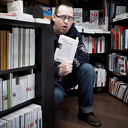 """PARIS, FRANCE. FEBRUARY 2012, 8. Yves Martin, bookseller and owner of his own shop """"Les Buveurs d'Encre"""", where the shooting took place. He's holding one of his favorite books of the moment, """"Crooked Letter, crooked letter"""" (""""Le retour de Silas Jones""""). Photo: Antoine Doyen"""