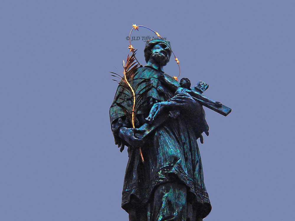 Looking up at the bronze statue of St. John Nepomuk on the Charles Bridge, Prague.  His figure, shown from the knees up, holds a crucifix and a gilded palm branch, & wears a gilded halo with 5 stars  Plain blue sky beyond.  The martyred saint's facial expression is mournful; he was killed and thrown from this bridge in 1393 as a result of a church-state struggle between the Kings of Bohemia and the Pope.  The statue was made by Jan Brokoff in 1683.
