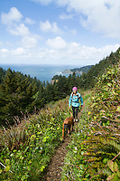 Young woman hiking on the Oregon Coast Trail in Oswald West State Park, OR.