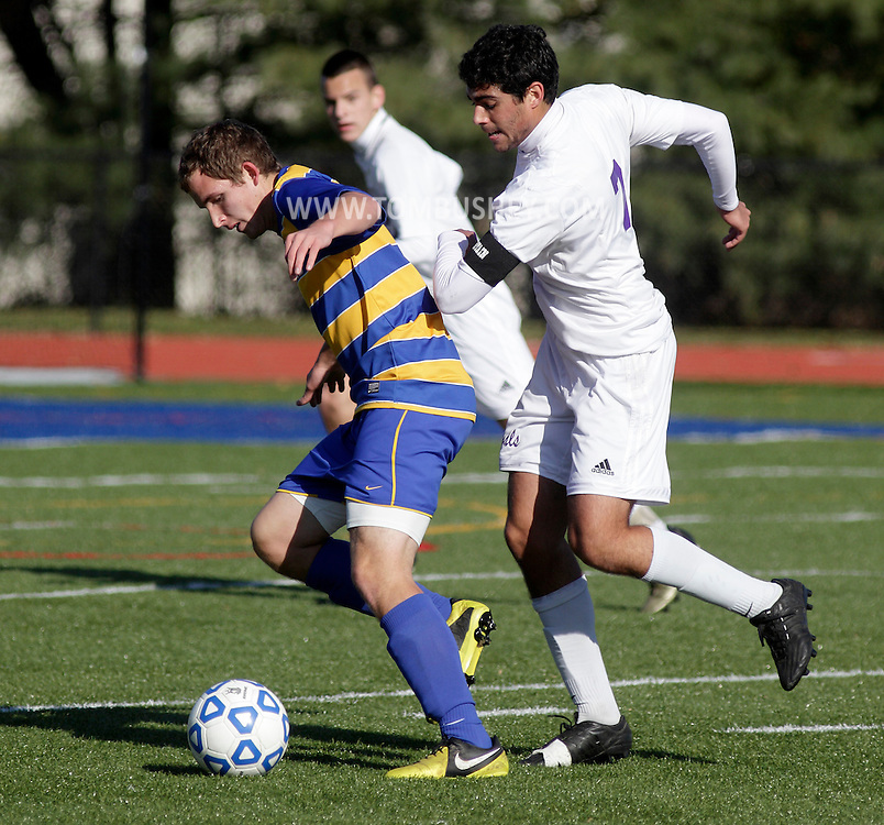 Lansing's Nate McIntosh, left, pushes the ball past Port Jefferson's Gerard Racanelli during the Class C state championship game at Faller Field in Middletown on Sunday, Nov. 18, 2012.