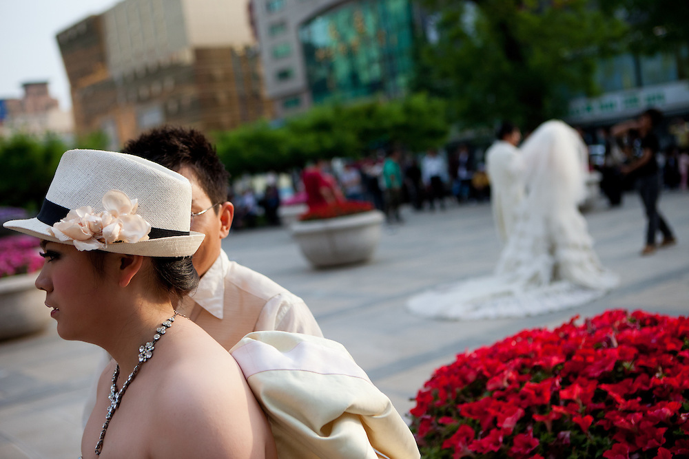 Just married. Couples getting photographed after their weddings, on a public square in the center of Beijing. Beijing is the capital of the People's Republic of China and one of the most populous cities in the world with a population of 19,612,368 as of 2010.