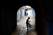 A young boy stands with his bicycle under a covered arch passageway as three men walk down an alley in the medina of Chefchaouen, Morocco.