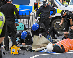Pictured: Specialist officers cut free one of the protesters, who is then led away to be checked over by paramedics before being detained.<br /> <br /> Climate change protesters blocked roads in the city centre including Lothian Road, where they chained themselves together inside concrete pipes meaning the police had to bring in specialist cutting equipment and teams to remove them, causing severe traffic disruption.<br /> <br /> © Dave Johnston / EEm