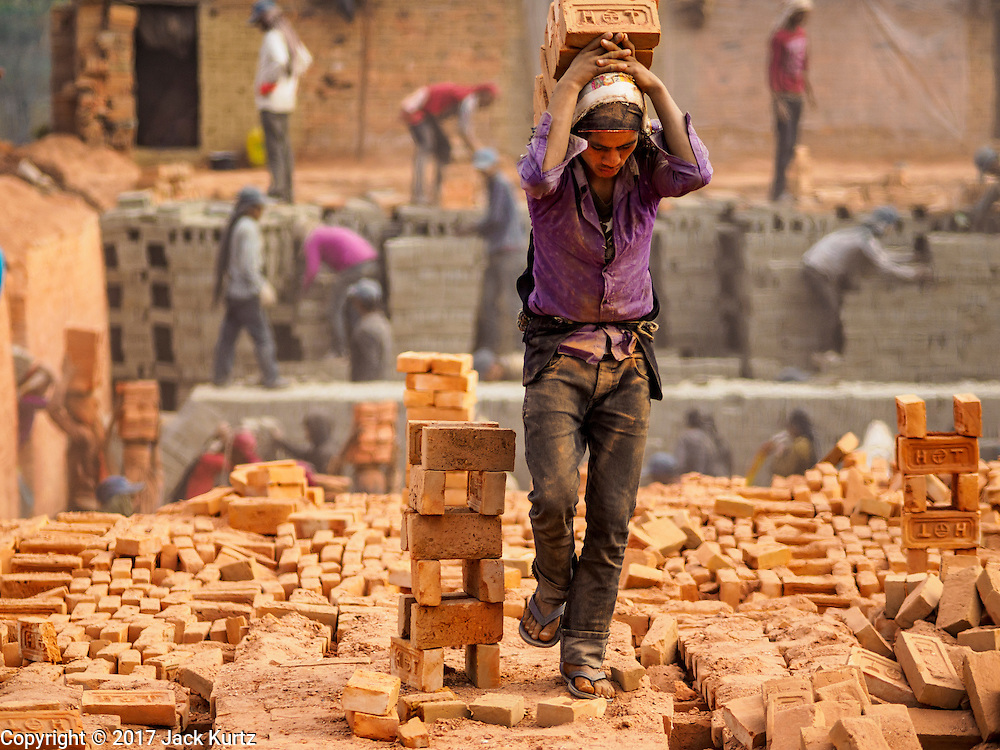 03 MARCH 2017 - BAGMATI, NEPAL: A worker carries baked and finished bricks to a waiting truck while other workers, in the background, stack wet, unbaked, bricks in the kiln at a brick factory in Bagmati, near Bhaktapur. The wet bricks are gray in color. They turn their characteristic red after they are baked in the kiln. There are almost 50 brick factories in the valley near Bagmati. The brick makers are very busy making bricks for the reconstruction of Kathmandu, Bhaktapur and other cities in the Kathmandu valley that were badly damaged by the 2015 Nepal Earthquake. The brick factories have been in the Bagmati area for centuries because the local clay is a popular raw material for the bricks. Most of the workers in the brick factories are migrant workers from southern Nepal.       PHOTO BY JACK KURTZ