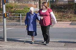 Carer helping elderly woman cross the road.