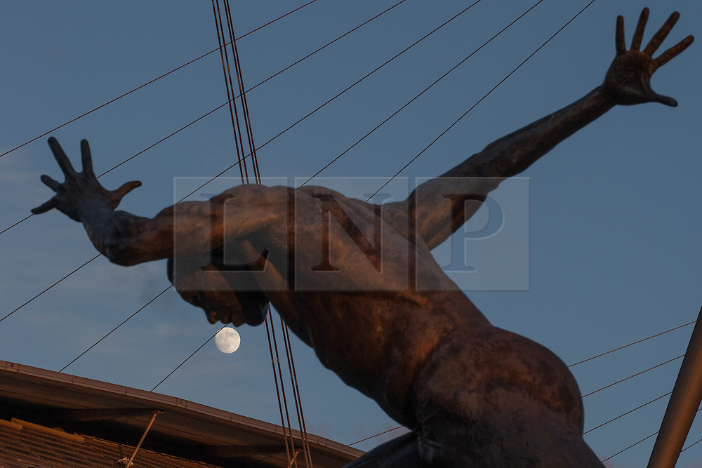 """© Licensed to London News Pictures . 12/05/2014 . Manchester , UK . The moon rising above the Etihad Stadium in Manchester this evening (12th May 2014) , with the silhouette of the statue """" The Runner """" as Manchester City celebrate their Premier League win this evening . Photo credit : Joel Goodman/LNP"""