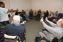 Trainer with service users, some in wheelchairs, doing specially adapted exercises for limited mobility at resource for people with physical and sensory impairment.