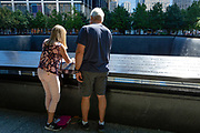 New York, NY - 7 September 2011. As the 20th anniversary of the attacks on the World Trade Center in New York approaches, people start to gather at the 9/11 Memorial site in lower Manhattan. A woman and a man make rubbings of names inscribed in the memorial parapet.