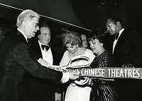 """1979 (L to R) William Hertz, Ted Mann, Rhonda Fleming, Councilwoman Peggy Stevenson and Mayor Tom Bradley during the grand opening ribbon cutting ceremony of Mann's Chinese Theaters #2 & #3 theaters during the premiere of """"Hurricane""""."""