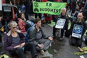 Buddhist environmental activists meditate and protest about Climate Change during the blockade at the junction at Bank in the heart of the capitals financial district, the City of London aka the Square Mile, on the seventh day of a two-week prolonged worldwide protest by members of Extinction Rebellion, on 14th October 2019, in London, England.