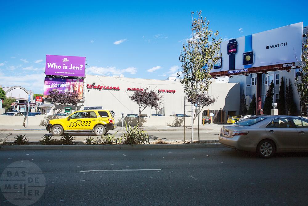 De Walgreens op de kruising van Broadway en Van Ness Avenue in San Francisco met een reclamebord voor de Apple iWatch. De Amerikaanse stad San Francisco aan de westkust is een van de grootste steden in Amerika en kenmerkt zich door de steile heuvels in de stad.<br /> <br /> The Walgreens at the intersection of Broadway and Polk Street in San Francisco. The US city of San Francisco on the west coast is one of the largest cities in America and is characterized by the steep hills in the city.